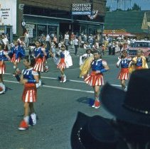 Image of The Round-Up Parade in September, 1959 - The Round-Up parade in September of 1959.  Children are cheerleading along 95th Street while Behrend's Hardware is visible in the background.