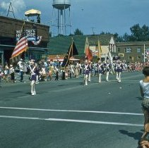 Image of The Round-Up Parade in September, 1959 - The Round-Up parade in September of 1959.  Young men are marching along 95th street holding a variety of flags.  Behrends Hardware, Sinclair Service Station, and the Oak Lawn Water Tower are visible in the background.