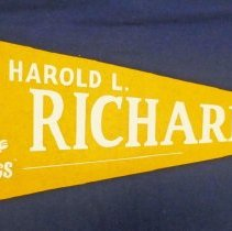 Image of Harold L. Richards High School Pennant  - This item is a pennant from Harold L. Richards High School. It is yellow and white in color with the image of a bulldog on the left side.