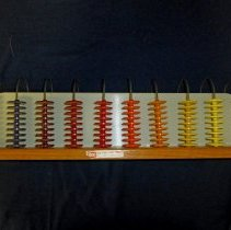 Image of Ideal School Supply Company Abacus - This item is a teaching abacus produced by the Ideal School Supply Company located at 11000 LaVergne in Oak Lawn.  It features a number of colored plastic chips and metal rings mounted to a wooden base.