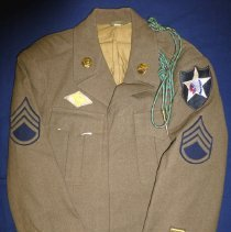 Image of Cather Munro's WWII Army Uniform - This item is a United States Army uniform from World War II.  The jacket has several different rank insignias and pins attached to it.  It was owned by Cathel Munro, a former Oak Lawn resident who served in the armed forces.