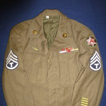 Image of Harold Lawson WWII Army Uniform Jacket - This item is a United States Army uniform from World War II.  The jacket has several different rank insignias, pins, and bars attached to it.  It was owned by Harold Lawson, a former area resident who served in the armed forces.