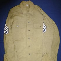 Image of Harold Lawson WWII Army Uniform Shirt - This item is a United States Army uniform from World War II.  The shirt has several different rank insignias attached to it.  It was owned by Harold Lawson, a former area resident who served in the armed forces.