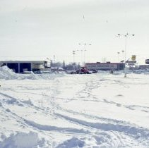 Image of 1967 Snowstorm - This is a photograph of the 1967 snowstorm.  It features the parking lot of the Green Oaks Shopping Center covered in snow. From left to right are Hillman Brothers, Shopper's World, LL Fish Furniture and Nelson Brothers.