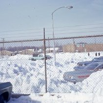 Image of 1967 Snowstorm - This is a photograph of the 1967 snowstorm.  It features a parking lot and vehicles covered in snow. Directly ahead is the Envoy Apartment Motel on Columbus Drive and visible on the right is the is the Midway Inn and Suites motel.