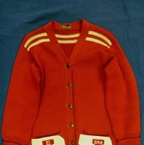"Image of Blue Island Community High School Sweater  - This item is a sweater worn by Mary Lou ""Farino"" Harker during her tenure at Blue Island Community High School.  It is red in color and features several white patches including one for cheerleading.  Prior to the opening of the Oak Lawn High Schools, some local residents attended Blue Island High."
