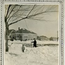 Image of Walter and Rhoda Zuschlag - This is a photograph taken from the porch of 9732 South Tulley Avenue.  It looks across the street to the east (and a little to the north).  Walter Emil-Bruno Zuschlag and Rhoda Marie Zuschlag can be seen shoveling their driveway. The house in the background is located at 9725 South Tulley Avenue, Oak Lawn.