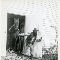 "Image of Oak Lawn Round Up Days Thief - This is a photograph of the Oak Lawn Round Up ""thief"". He is sneaking out with his horse and gun drawn. During the event, many participants would dress up on Western style clothing and play different characters."