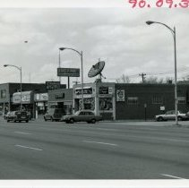 Image of 5200 West Block of 95th Street - This is a photograph of the 5200 block of 95th street focusing on the north side near Tulley Avenue. American Health Foods, Doll House Pizza, T.H.E. Safeman, and Krauss' Gaslite Lounge are all visible.