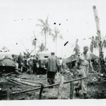 Image of World War II Photograph - This is a photograph taken in the Pacific Theater during the Second World War. It features a group of soldiers and two cars, and the exact location is unknown.