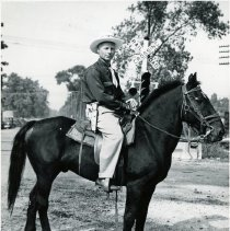 Image of Roland Beckley on Horseback - This is a photograph of Roland Beckley on his black horse. The photograph was taken at the Oak Lawn Round Up Days in 1950.