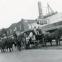Image of Oak Lawn Round-Up Days - This is a photograph from the Oak Lawn Round-Up Days. This image shows men holding up a stagecoach in front of the Oak Lawn Trust & Savings Bank located near 95th Street and 53rd Court.