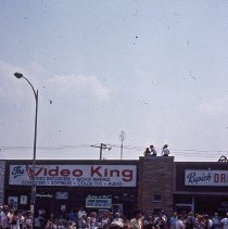 Image of 1983 Oak Lawn Fest Parade - This item is a slide of the 1983 Oak Lawn Fest Parade. It features an old fashioned vehicle moving down 95th Street.  The Video King and Rupich's Drugs, located at 5207 and 5209 West 95th Street, are visible in the background.