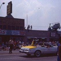 Image of 1983 Oak Lawn Fest Parade - This item is a slide of the 1983 Oak Lawn Fest Parade.  It features a vehicle sponsored by Jack Thompson Oldsmobile, and carrying McDonald's characters, moving down 95th Street.  Oak Lawn Office Supply, S&S Men's Wear, the Village Bath Shop and other businesses are visible in the background.