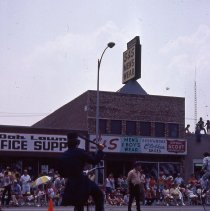 Image of 1983 Oak Lawn Fest Parade - This item is a slide of the 1983 Oak Lawn Fest Parade.  It features an old fashioned bicycle moving down 95th Street.  Oak Lawn Office Supply and S&S Men's Wear are visible in the background.