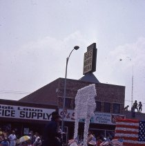 Image of 1983 Oak Lawn Fest Parade - This item is a slide of the 1983 Oak Lawn Fest Parade.  It features an old fashioned bicycle and Concordia Federal Savings float moving down 95th Street.  Oak Lawn Office Supply and S&S Men's Wear are visible in the background.