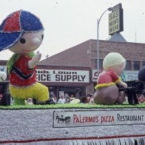 Image of 1983 Oak Lawn Fest Parade - This item is a slide of the 1983 Oak Lawn Fest Parade.  It features a Palermo's Pizza Restaurant float moving down 95th Street.  Rupich's Drugs, Oak Lawn Office Supply and S&S Men's Wear are visible in the background.