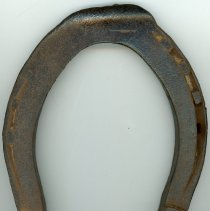 Image of Horseshoe  - This item is a horseshoe worn by a draft horse at an unknown date. I may have been used it Oak Lawn in the late 19th or early 20th Century. There is a small white tag listing a number provided by the Oak Lawn Historical Society.