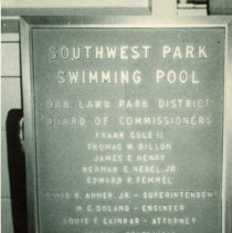 Image of Southwest Park Swimming Pool Plaque - This is a photograph of the Dedication Plaque at the Southwest Park Swimming Pool.  The Plaque lists the names of the Oak Lawn Park District Board of Commissioners. Listed are: Frank Cole II, Thomas Dillon, James E. Henery, Herman C. Nebel, Junior, Edward P. Temmel, Lewis Ahner, W.C. Doland, Louis F. Cainkar, Empire Piping Corporation, and Chester Product, Incorporated.