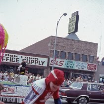 Image of 1983 Oak Lawn Fest Parade - This item is a slide of the 1983 Oak Lawn Fest Parade.  It features a Budweiser character walking down 95th Street. Oak Lawn Office Supply and S&S Men's Wear are visible in the background.