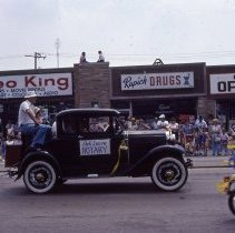 Image of 1983 Oak Lawn Fest Parade - This item is a slide of the 1983 Oak Lawn Fest Parade.  It features a vehicle sponsored by the Oak Lawn Rotary Club moving down 95th Street. The Video King, Rupich's Drugs and Oak Lawn Office Supply are visible in the background.