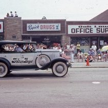 Image of 1983 Oak Lawn Fest Parade - This item is a slide of the 1983 Oak Lawn Fest Parade.  It features an antique vehicle moving down 95th Street. The Video King, Rupich's Drugs and Oak Lawn Office Supply are visible in the background.