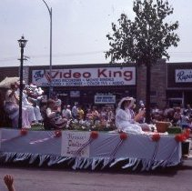 Image of 1983 Oak Lawn Fest Parade - This item is a slide of the 1983 Oak Lawn Fest Parade.  It features a float sponsored by the Krauss' Gaslite Lounge moving down 95th Street. Swell Elegante Gifts of Distinction, The Video King, and Rupich's Drugs are visible in the background.