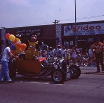 Image of 1983 Oak Lawn Fest Parade - This item is a slide of the 1983 Oak Lawn Fest Parade.  It features an old fashioned vehicle moving down 95th Street. Mal's Men's Shop, Swell Elegante Gifts of Distinction and The Video King are visible in the background.