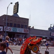 Image of 1983 Oak Lawn Fest Parade - This item is a slide of the 1983 Oak Lawn Fest Parade.  It features a Native American performer on 95th Street. S&S Men's Wear is visible in the background.