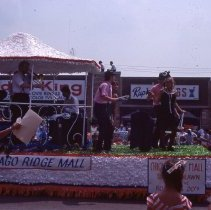 Image of 1983 Oak Lawn Fest Parade - This item is a slide of the 1983 Oak Lawn Fest Parade.  It features a float sponsored by Chicago Ridge Mall moving down 95th Street. The Video King, Rupich's Drugs and Oak Lawn Office Supply are visible in the background.