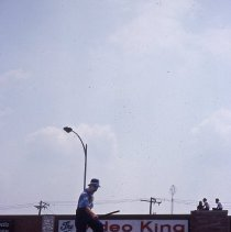 Image of 1983 Oak Lawn Fest Parade - This item is a slide of the 1983 Oak Lawn Fest Parade. It features a performer on stilts moving down 95th Street. The Video King is visible in the background.