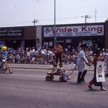 Image of 1983 Oak Lawn Fest Parade - This item is a slide of the 1983 Oak Lawn Fest Parade. It features a group of clowns moving down 95th Street. Mal's Men's Shop, Swell Elegante Gifts of Distinction, The Video King and Rupich's Drugs are visible in the background.