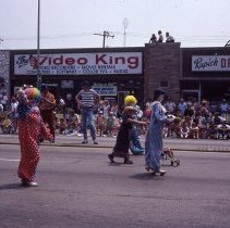 Image of 1983 Oak Lawn Fest Parade  - This item is a slide of the 1983 Oak Lawn Fest Parade. It features a group of clowns moving down 95th Street. Swell Elegante Gifts of Distinction, The Video King and Rupich's Drugs are visible in the background.