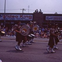 Image of 1983 Oak Lawn Fest Parade - This item is a slide of the 1983 Oak Lawn Fest Parade. It features the Rampart Lion Pipe Band moving down 95th Street. The Video King and Rupich's Drugs are visible in the background.