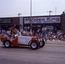 Image of 1983 Oak Lawn Fest Parade - This item is a slide of the 1983 Oak Lawn Fest Parade. It features a vehicle sponsored by Laura's Hair Design moving down 95th Street. Swell Elegante Gifts of Distinction, The Video King and Rupich's Drugs are visible in the background.