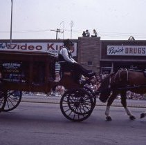 Image of 1983 Oak Lawn Fest Parade - This item is a slide of the 1983 Oak Lawn Fest Parade.  It features an antique hearse from Robert J. Sheehy & Sons Funeral Home moving down 95th Street. The Video King, Rupich's Drugs and Oak Lawn Office Supply are visible in the background.