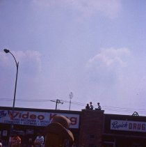 Image of 1983 Oak Lawn Fest Parade - This item is a slide of the 1983 Oak Lawn Fest Parade.  It features a costumed performer on 95th Street. The Video King and Rupich's Drugs are visible in the background.