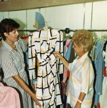 Image of A Weekend in the Life of Oak Lawn - This is a photograph of everyday life in Oak Lawn during 1987. It features Andrea Wulff of The House of Mary clothing store showing a dress to an unidentified customer. The House of Mary was located at 9519 S. Cicero Avenue in the Green Oaks Shopping Center.