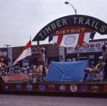 Image of 1983 Oak Lawn Fest Parade - This item is a slide of the 1983 Oak Lawn Fest Parade. It features a vehicle sponsored by the Boy Scouts Timber Trails District moving down 95th Street. Mal's Men's Shop, Swell Elegante Gifts of Distinction and The Video King are visible in the background.