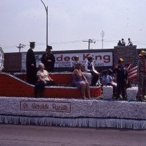 Image of 1983 Oak Lawn Fest Parade - This item is a slide of the 1983 Oak Lawn Fest Parade. It features a vehicle sponsored by St. Gerald's Parish  moving down 95th Street. Swell Elegante Gifts of Distinction, The Video King and Rupich's Drugs are visible in the background.