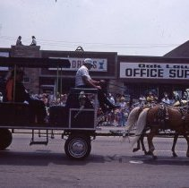 Image of 1983 Oak Lawn Fest Parade - This item is a slide of the 1983 Oak Lawn Fest Parade. It features a small cart pulled by horses moving down 95th Street. The Video King, Rupich's Drugs, Oak Lawn Office Supply and S&S Men's Wear are visible in the background.