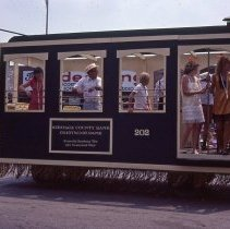 Image of 1983 Oak Lawn Fest Parade - This item is a slide of the 1983 Oak Lawn Fest Parade. It features a trolley sponsored by Heritage County Bank and Crestwood Bank moving down 95th Street. Swell Elegante Gifts of Distinction, The Video King and Rupich's Drugs are visible in the background.