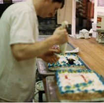 Image of A Weekend in the Life of Oak Lawn - This is a photograph of everyday life in Oak Lawn during 1987. It features Bill Love decorating cakes at Tuzik's Bakery located at 4955 W. 95th Street.