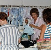 Image of A Weekend in the Life of Oak Lawn - This is a photograph of everyday life in Oak Lawn during 1987. It features Anne Langland (facing camera) helping Linda Malone (blue and white horizontal strip shirt) in Pride 'N Joy located at 9517 S. Cicero Avenue in the Green Oaks Shopping Center. The customer on the left is unidentified.