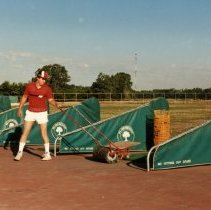Image of A Weekend in the Life of Oak Lawn - This is a photograph of everyday life in Oak Lawn during 1987. It features Bill Chorley picking up golf balls at the Stony Creek Driving Range located at 102nd and Mayfield. The communications antenna which stands in the Oak Lawn Public Works yard located at 98th and Central Avenue can be seen in the background.