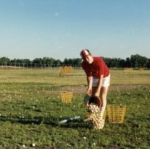 Image of A Weekend in the Life of Oak Lawn - This is a photograph of everyday life in Oak Lawn during 1987. It features Bill Chorley (foreground) and Bill Olsen (background) collecting golf balls on the Stony Creek Driving Range located at 102nd and Mayfield.