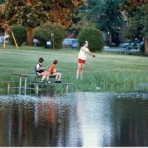 Image of A Weekend in the Life of Oak Lawn - This is a photograph of everyday life in Oak Lawn during 1987. It features 8 year-old Chad Bruntjens and 10 year-old Randy Bruntjens and an unidentified man believed to be their father, fishing at the pond at Memorial Park, also known as Rocketship Park, near 102nd St. and Mayfield Avenue.