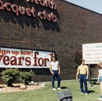 Image of A Weekend in the Life of Oak Lawn - This is a photograph of everyday life in Oak Lawn during 1987. It features Bill Thompson, Carl Greschak, and Wanda Stavis on the lawn of the Chicago Health & Racquet Club located at 6700 W. 95th Street. A sign thanking Oak Lawn for their business and improvements to the club can be seen in the background.