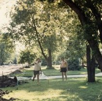 Image of A Weekend in the Life of Oak Lawn - This is a photograph of everyday life in Oak Lawn during 1987. It features Bob Murphy and Ken Nelson playing a game of horseshoes near a street under construction.
