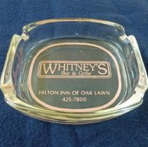 Image of Whitney's Bar and Grille Ashtray - This item is an ashtray from Whitney's Bar and Grille located in the Hilton Inn of Oak Lawn at 9333 South Cicero Avenue. It features the bar's logo in purple lettering.